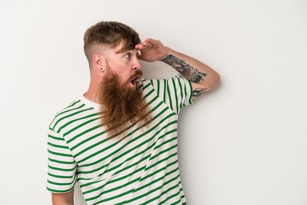 額に手を置いて遠くを見ている白い背景で隔離の長いひげを持つ若い白人生姜男。