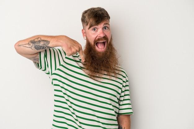 シャツのコピースペース、誇りと自信を持って手で指している白い背景の人に分離された長いひげを持つ若い白人生姜男