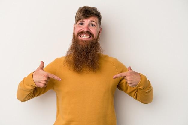 シャツのコピースペースを手で指している白い背景の人に分離された長いひげを持つ若い白人生姜男、誇りと自信を持って