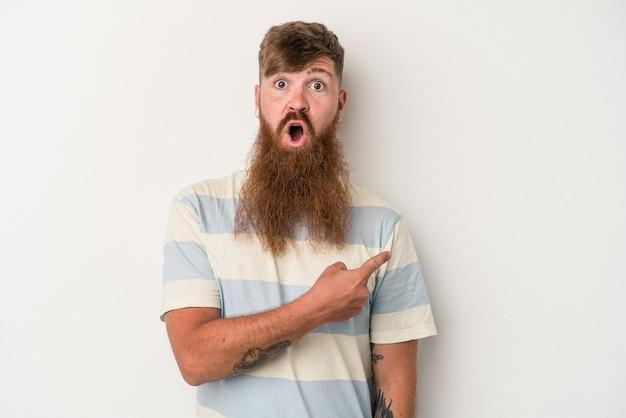 側面を指している白い背景で隔離の長いひげを持つ若い白人生姜男