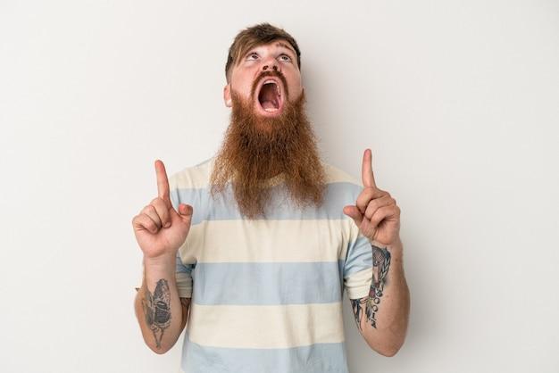 口を開けて逆さまを指している白い背景に分離された長いひげを持つ若い白人生姜男。