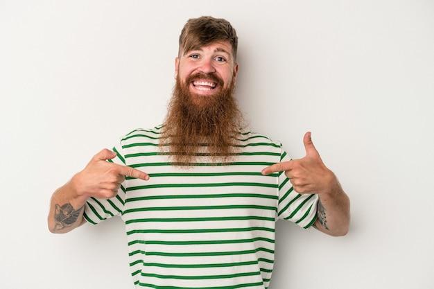 흰색 배경에 격리된 긴 수염을 가진 젊은 백인 생강 남자는 손가락으로 아래를 가리키며 긍정적인 느낌을 줍니다.