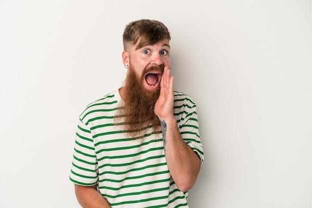 白い背景で隔離の長いひげを持つ若い白人の生姜男は大声で叫び、目を開いたままにし、手を緊張させます。