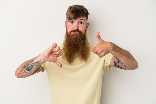 親指を上に、親指を下に示す白い背景で隔離の長いひげを持つ若い白人生姜男、難しい選択の概念