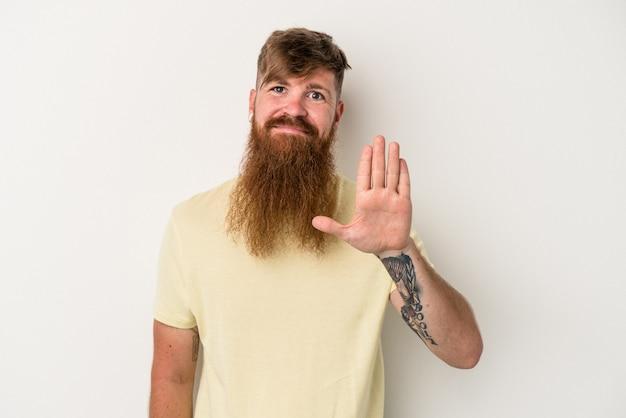 白い背景に分離された長いひげを持つ若い白人の生姜男は、指で5番を示して陽気に笑っています。