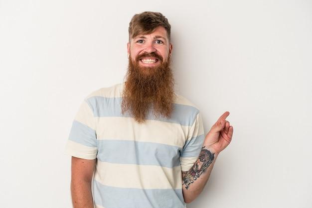 白い背景に分離された長いひげを持つ若い白人の生姜男は、人差し指を離れて元気に指して微笑んでいます。