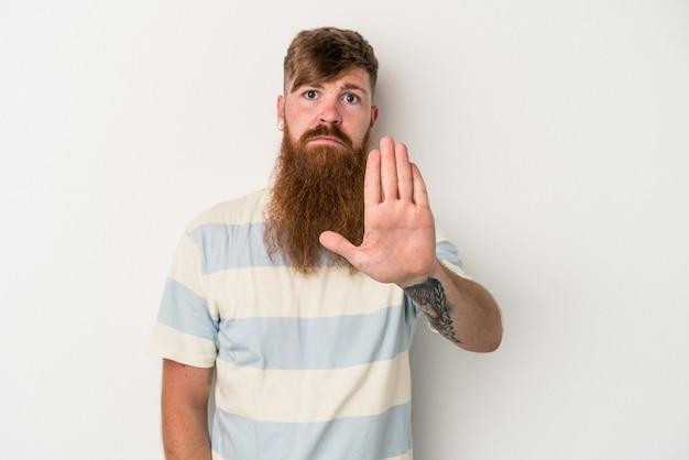 白い背景で隔離の長いひげを持つ若い白人の生姜男は、一時停止の標識を示している手を伸ばして立って、あなたを防ぎます。
