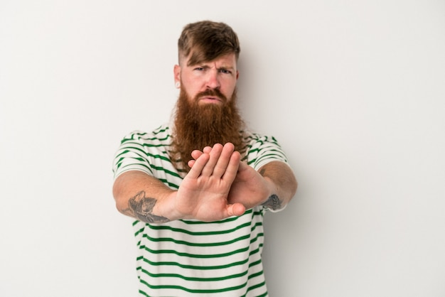 白い背景で隔離の長いひげを持つ若い白人生姜男は、一時停止の標識を示している手を伸ばして立って、あなたを防ぎます。