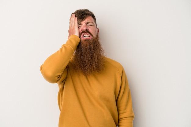Молодой кавказский рыжий мужчина с длинной бородой на белом фоне устал и очень сонный, держа руку на голове.