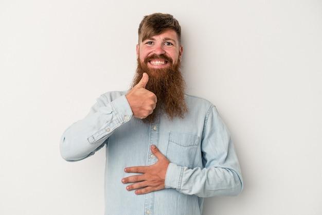 흰색 배경에 격리된 긴 수염을 가진 젊은 백인 생강 남자는 배를 만지고 부드럽게 미소 짓고 식사와 만족 개념을 합니다.