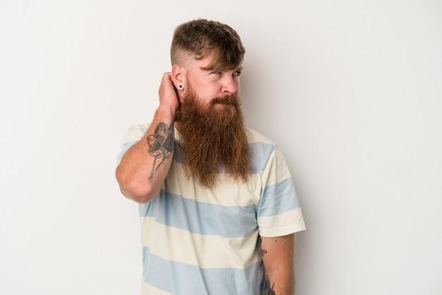 頭の後ろに触れて、考えて、選択をする白い背景に分離された長いひげを持つ若い白人生姜男。