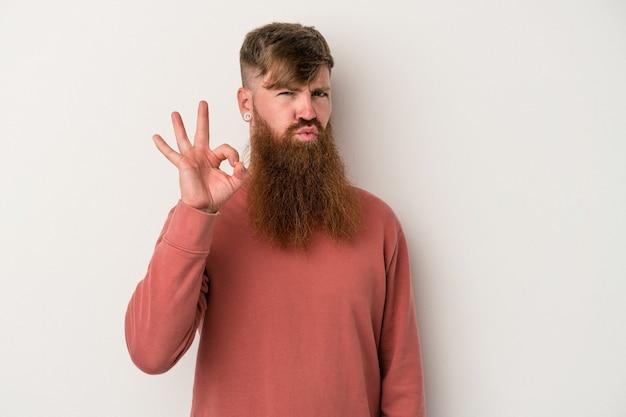 白い背景で隔離の長いひげを持つ若い白人生姜男は目をまばたきし、手で大丈夫なジェスチャーを保持します。