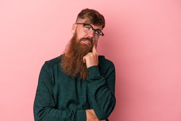 Young caucasian ginger man with long beard isolated on pink background crying, unhappy with something, agony and confusion concept.