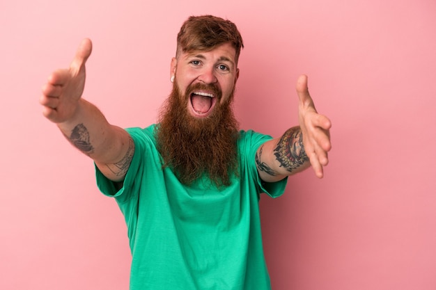 Young caucasian ginger man with long beard isolated on pink background feels confident giving a hug to the camera.