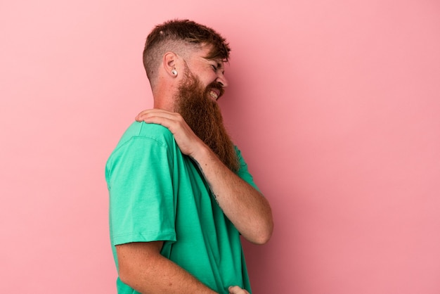 Young caucasian ginger man with long beard isolated on pink background having a shoulder pain.