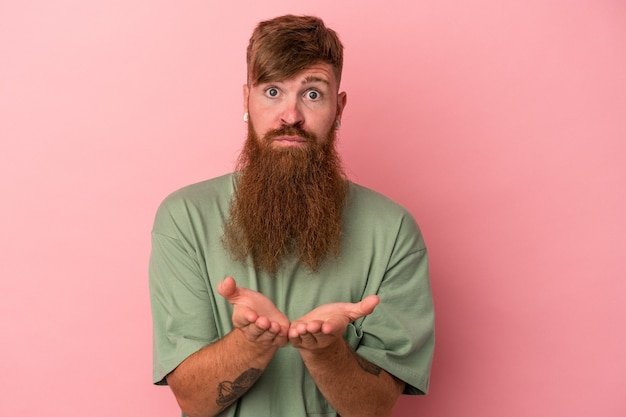 Young caucasian ginger man with long beard isolated on pink background holding something with palms, offering to camera.