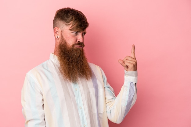Young caucasian ginger man with long beard isolated on pink background pointing with finger at you as if inviting come closer.