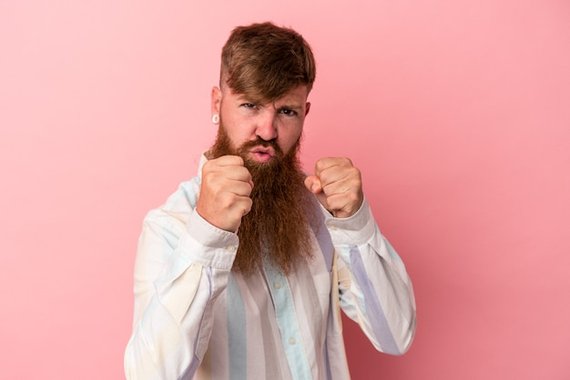 Young caucasian ginger man with long beard isolated on pink background showing fist to camera, aggressive facial expression.
