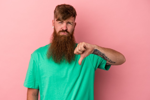 Young caucasian ginger man with long beard isolated on pink background showing thumb down, disappointment concept.