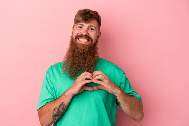 Young caucasian ginger man with long beard isolated on pink background smiling and showing a heart shape with hands.