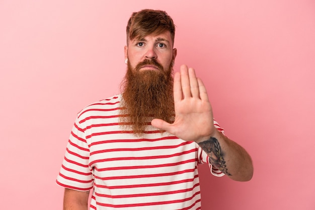 Young caucasian ginger man with long beard isolated on pink background standing with outstretched hand showing stop sign, preventing you.