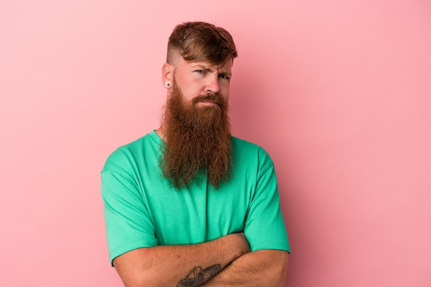 Young caucasian ginger man with long beard isolated on pink background suspicious, uncertain, examining you.