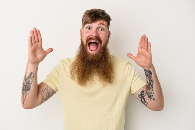 Young caucasian ginger man with long beard isolated on white background celebrating a victory or success, he is surprised and shocked.