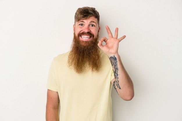 Young caucasian ginger man with long beard isolated on white background cheerful and confident showing ok gesture.