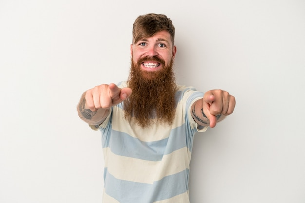 Young caucasian ginger man with long beard isolated on white background cheerful smiles pointing to front.