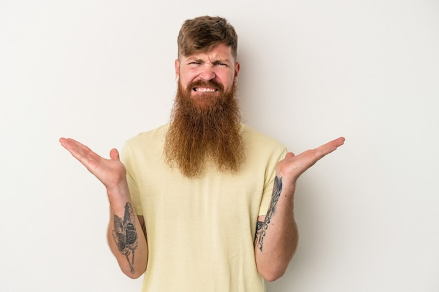 Young caucasian ginger man with long beard isolated on white background confused and doubtful shrugging shoulders to hold a copy space.