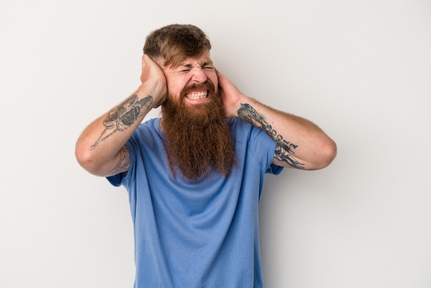 Young caucasian ginger man with long beard isolated on white background covering ears with hands.
