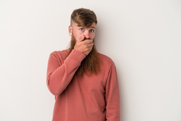 Young caucasian ginger man with long beard isolated on white background covering mouth with hands looking worried.
