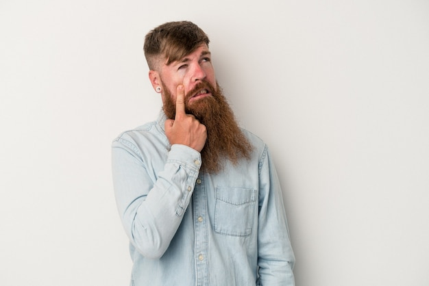 Young caucasian ginger man with long beard isolated on white background crying, unhappy with something, agony and confusion concept.