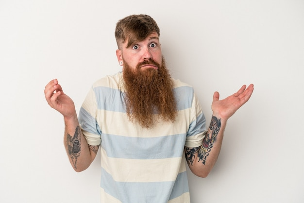 Young caucasian ginger man with long beard isolated on white background doubting and shrugging shoulders in questioning gesture.