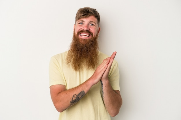 Young caucasian ginger man with long beard isolated on white background feeling energetic and comfortable, rubbing hands confident.