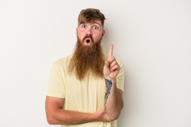 Young caucasian ginger man with long beard isolated on white background having some great idea, concept of creativity.
