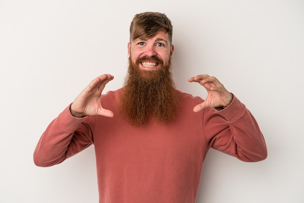 Young caucasian ginger man with long beard isolated on white background holding something with palms, offering to camera.