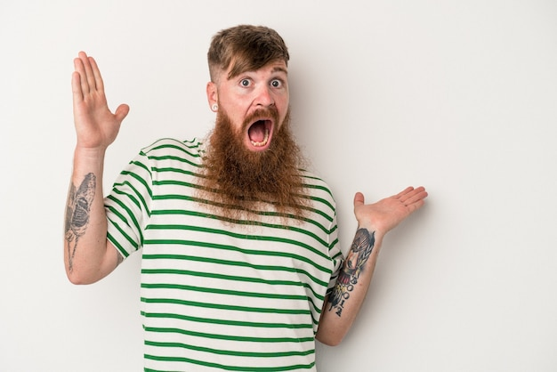 Young caucasian ginger man with long beard isolated on white background holds copy space on a palm, keep hand over cheek. amazed and delighted.