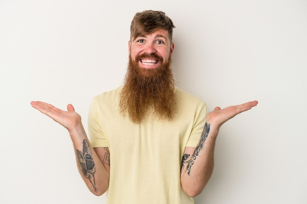 Young caucasian ginger man with long beard isolated on white background makes scale with arms, feels happy and confident.