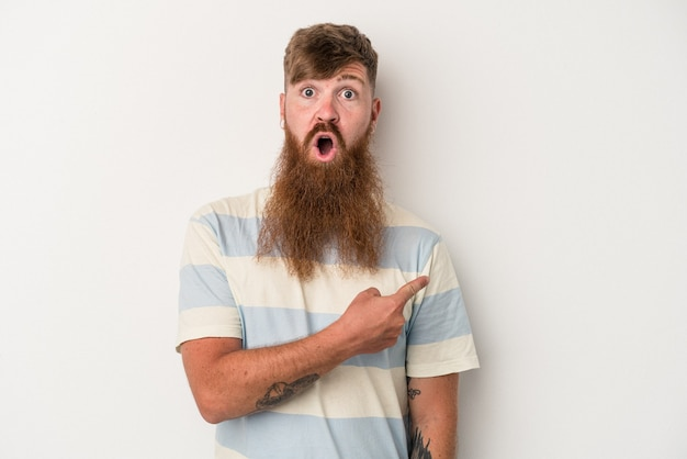 Young caucasian ginger man with long beard isolated on white background pointing to the side