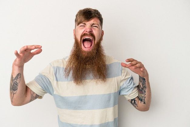 Young caucasian ginger man with long beard isolated on white background screaming to the sky, looking up, frustrated.