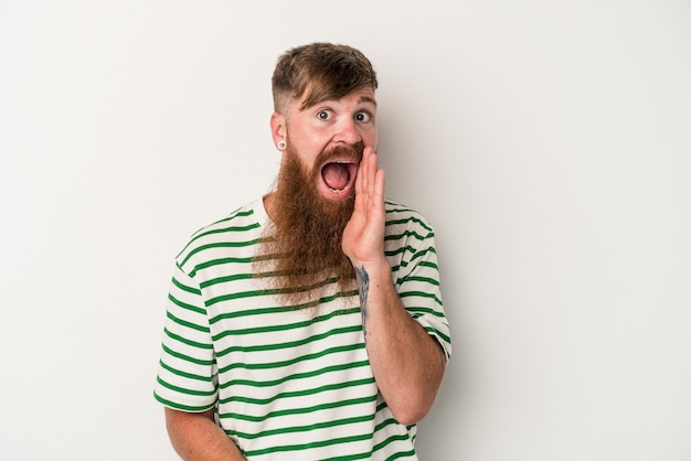 Young caucasian ginger man with long beard isolated on white background shouts loud, keeps eyes opened and hands tense.