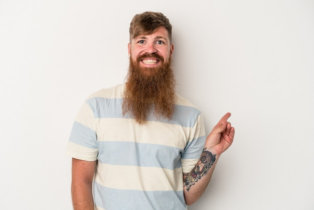 Young caucasian ginger man with long beard isolated on white background smiling cheerfully pointing with forefinger away.
