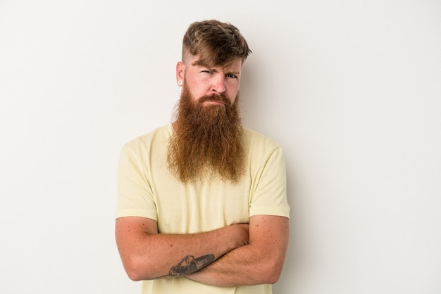 Young caucasian ginger man with long beard isolated on white background suspicious, uncertain, examining you.