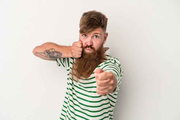 Young caucasian ginger man with long beard isolated on white background throwing a punch, anger, fighting due to an argument, boxing.