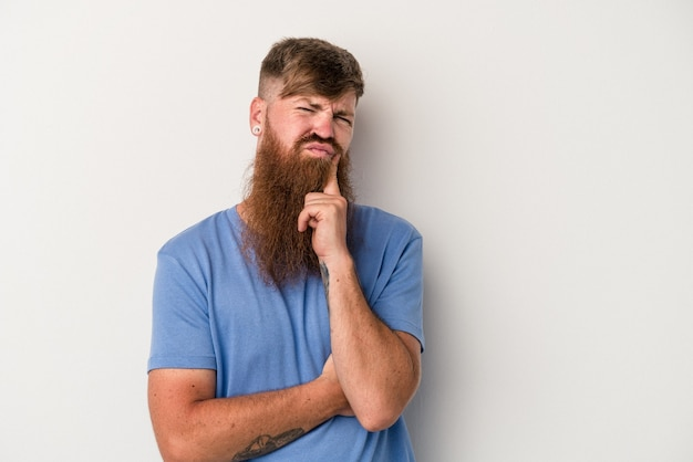 Young caucasian ginger man with long beard isolated on white background unhappy looking in camera with sarcastic expression.