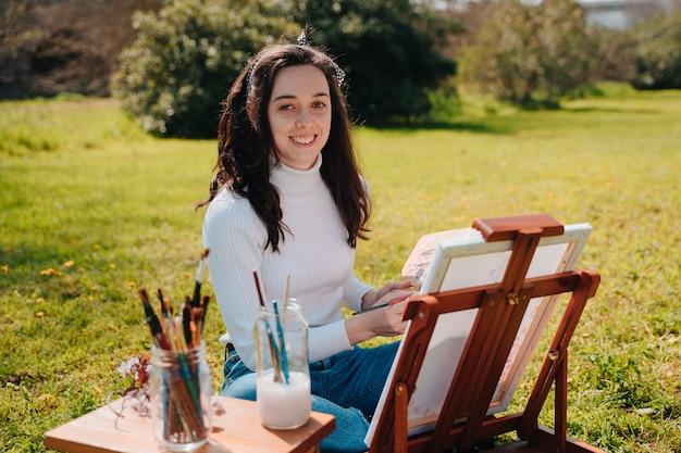 Молодая кавказская девушка, художник, рисует картины в парке в очень вдохновляющий день из-за красок окружающей среды.