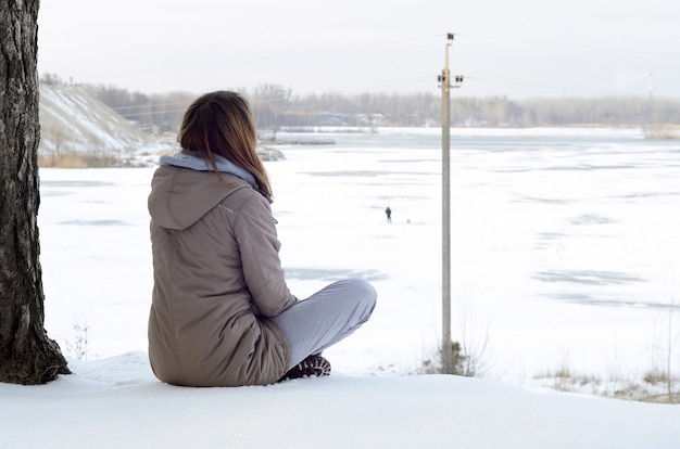 A young caucasian girl in a brown coat staring into the distance on the horizon line between the sky and the frozen lake in winter