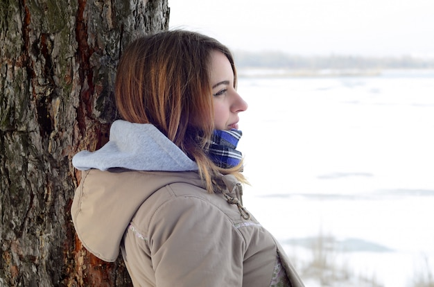 A young caucasian girl in a brown coat staring into the distance on the horizon