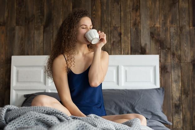 아침에 그의 방에 있는 침대에 앉아 커피를 마시는 백인 소녀